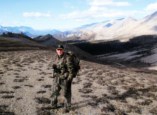With mountains looming in the background, Roger Rozema is ready to hunt as he stands in an open area during a recent caribou hunting excursion to the Canadas Northwest Territories.