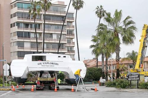 Lil' Explorers, a 58 foot long and 29 foot wide catamaran, waits to be lifted into Newport Bay as workers put together a crane near the Cannery Restaurant in Newport Beach on Thursday, Jan. 24.