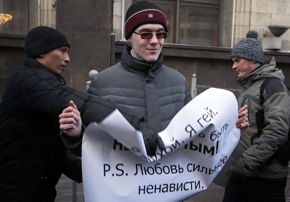 "A supporter of a bill banning ""homosexual propaganda"" tries to grab a poster from the hands of a gay rights activist during a protest near the State Duma in Moscow on Friday."