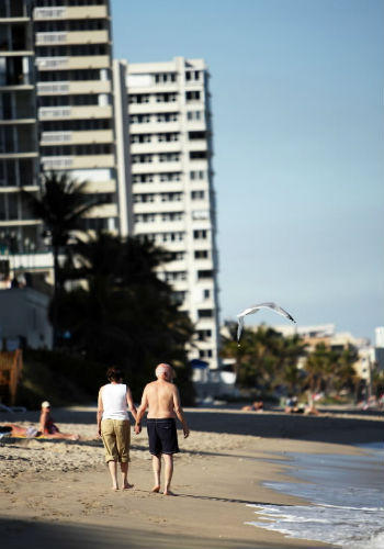 A couple walks along Galt Ocean Mile in Fort Lauderdale.