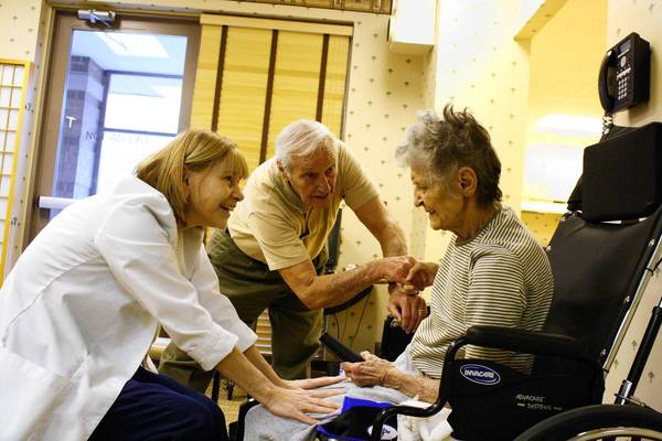 Robert Campo, middle, helps his wife Bernice with her physical therapy at Alden Des Plaines Rehabilitation and Health Care Center.
