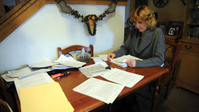 Shelli Lysic of Jerome looks over paperwork involved with the sexual discrimination claim she filed against Conemaugh Township Municipal Authority. Lysic is shown at her home on Friday.