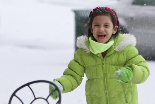Six-year-old Sofia Farley plays in the snow outside of Aromas in City Center late Friday afternoon.
