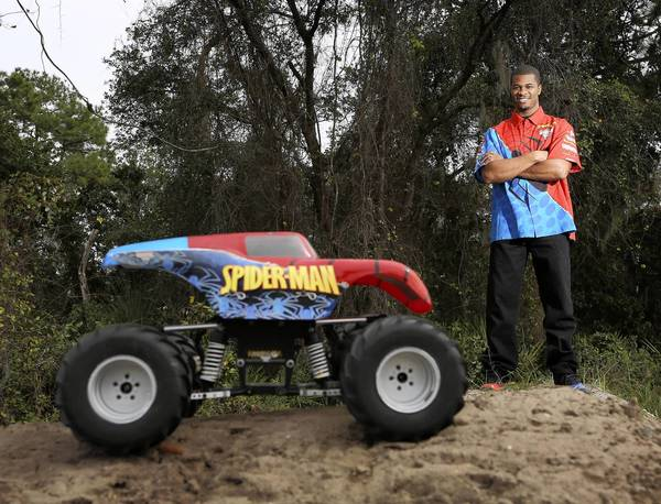 Bari Musawwir stands on a sand pile near his Ocoee home with his remote-controlled Spider-Man monster truck. Musawwir, the driver of the real Spider-Man truck, will compete in Monster Jam Saturday night at the Citrus Bowl in Orlando. He got his start racing the radio-controlled trucks.