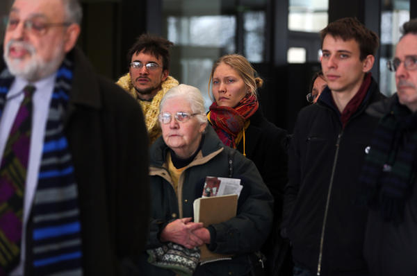 "Regina Bambrick-Rust, center in rear, stands with other supporters of the ""NATO 3"" as Michael Deutsch, a lawyer for the People's Law Office who represents Brian Church, speaks to the media at the Leighton Criminal Court Building in Chicago. Attorneys for three protesters asked today that the state's terrorism law be declared unconstitutional."