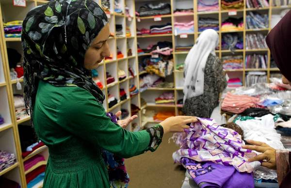 Mahum Tahir, 14, picks out scarves at Al-Anwar in Anaheim. Muslim women craving fashionable yet conservative apparel are getting a hand from local designers who are catering to trend-conscious women who want to follow Islam.
