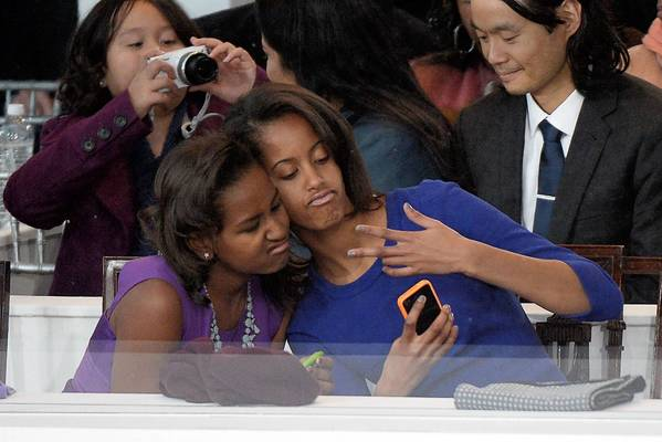Sasha, left, and Malia Obama take a photo of themselves on a cellphone during the presidential inaugural parade.