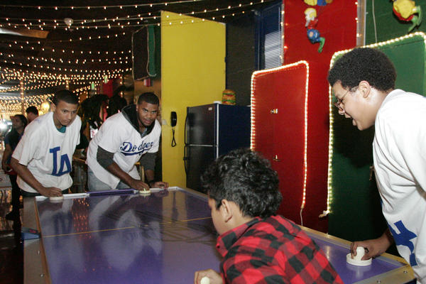 "Marquise Patterson, from left, plays air hockey with LA Dodgers' Kenley Jansen during the Dodgers 10th annual Community Caravan ""Pitching in the Community,"" which took place at Tobinworld in Glendale on Friday, January 25, 2013."