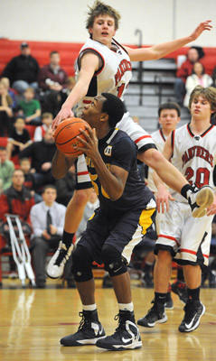Saucon Valley's Mike Kane (top) tries to block a shot by Notre Dame's Vincent Eze (bottom) during their Colonial League boys basketball game Friday.