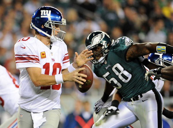 New York Giants quarterback Eli Manning (10) is pressured by Philadelphia Eagles defensive end Trent Cole (58) at Lincoln Financial Field in Philadelphia on Sunday.