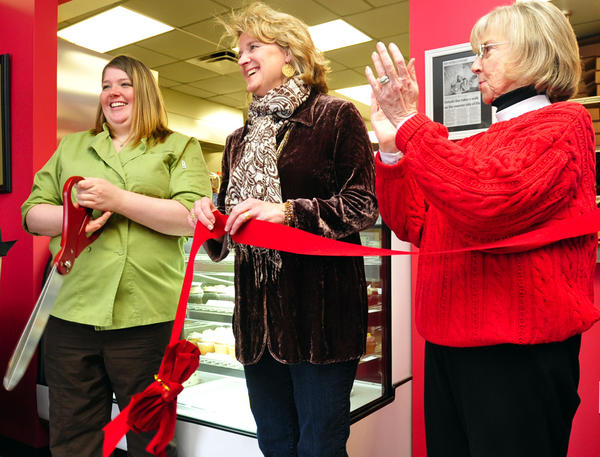 Cake Walk Specialty Cakes & Pastries partners Katie Martin, left, and Kathleen Murray are applauded by county commissioner Ruth Anne Callaham Friday as they celebrate their second year of business in South Pointe.
