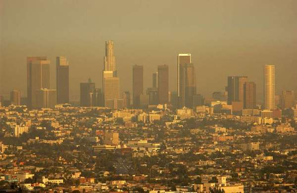 "Smog envelopes Los Angeles in this 2003 photograph. A new study says that ""waste heat"" from major cities influences global weather."