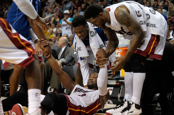 Miami Heat guard Dwyane Wade is helped up off the floor after scoring a basket and getting fouled during the first half against the Detroit Pistons, Friday, January 25, 2013, at AmericanAirlines Arena.