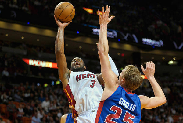 Miami Heat guard Dwyane Wade looks for a foul call as he scores over Detroit Pistons forward Kyle Singler during the first half of their game, Friday, January 25, 2013, at AmericanAirlines Arena.