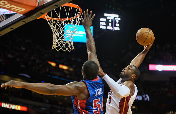 Miami Heat guard Dwyane Wade looks to dunk the ball over Detroit Pistons forward Jason Maxiell during the first half of their game, Friday, January 25, 2013, at AmericanAirlines Arena.