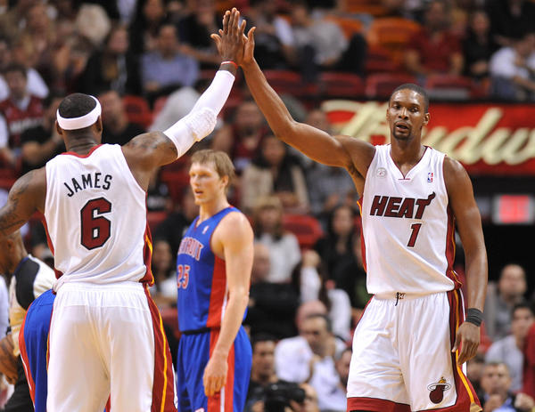 Miami Heat small forward LeBron James (left) greets center Chris Bosh (right) after Bosh was fouled during the first half against the Detroit Pistons at American Airlines Arena.