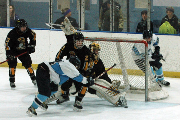 Petoskey senior forward Derek Smith (front) takes a shot on goal against Traverse City Central Friday at Griffin Arena. The Trojans defeated the Northmen, 8-0.