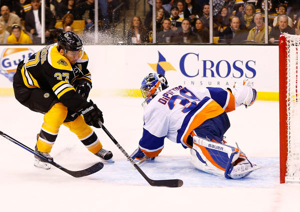 Patrice Bergeron #37 of the Boston Bruins scores a goal around Rick DiPietro #39 of the New York Islanders.