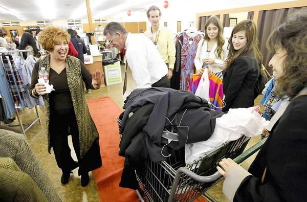 CEO Jerri Rosen, far left, laughs as Michael Holloway wheels a shopping basket full of men's jackets into the new Working Wardrobes Thrift Shop grand-opening celebration Thursday in Costa Mesa.