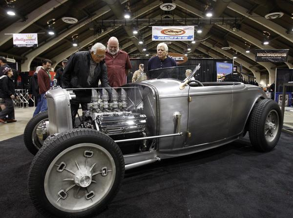 Albert Lugo, left, of Manhattan Beach, Mike Kusulandich of San Juan Capistrano and Anthonly Lugo of Vista, admire a bare-metal 1932 Ford Roadster highboy replica built by Pinkee's Rod Shop of Windsor, Colo.