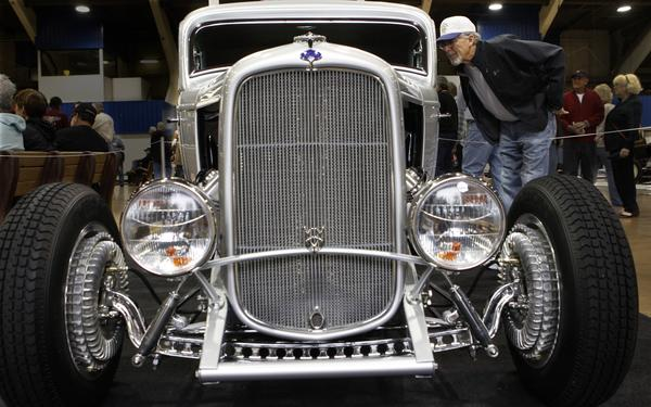 Clay Sheffrey of Glendale looks over a 1932 Ford chopped three-window highboy coupe owned by Bill Lindig of Houston at the 64th Grand National Roadster Show on Friday. So-Cal Speed Shop of Pomona performed the car's final assembly and finish. The car features a unique and rare flathead Ardun overhead conversion engine. Lindig's other car on display, a 1927 Ford Roadster, won the 2012 Most Beautiful Roadster Award at the show.