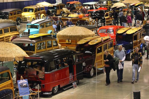 People tour the Woodies, Wagons & the Spirit of Aloha exhibit during the 64th Grand National Roadster Show at the Pomona Fairplex. The woody was introduced in 1910. The wood panels replaced steel, which became a scarcer commodity during World War I, helping fuel the woody's popularity.