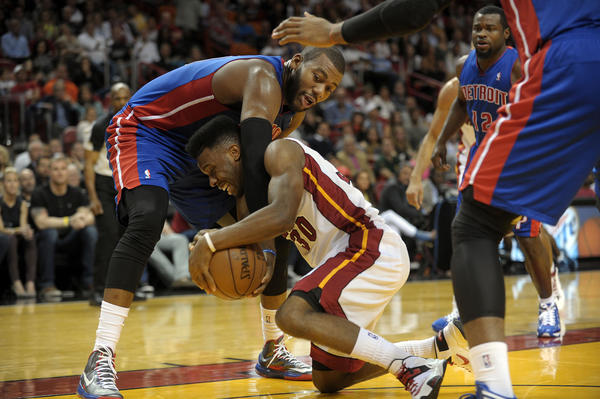 Miami Heat guard Norris Cole recovers the ball in front of Detroit Pistons center Greg Monroe during the first half of their game.