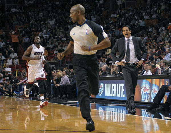 Miami Heat coach Erik Spoelstra and Dwyane Wade look to referee Tom Washington for a foul call against the Detroit Pistons.