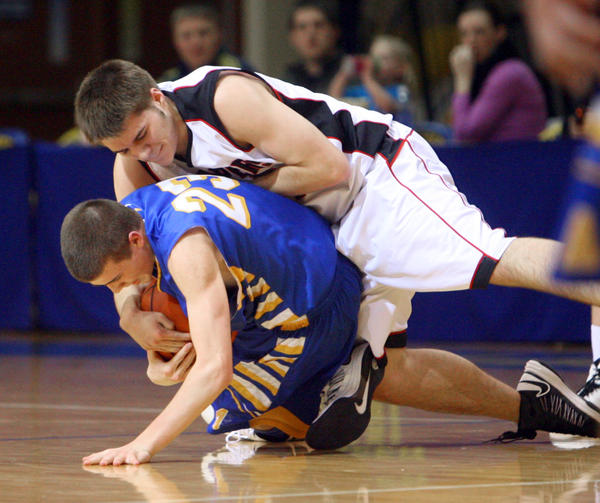 Aberdeen Central's Logan LeGrand (23) tries to keep the ball from Sturgis' Jeremy Guttierez, top, as they scramble on the floor during the first half of Friday night's game at the Golden Eagles Arena.