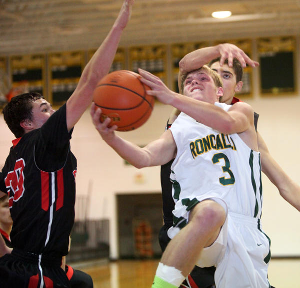 Aberdeen Roncalli's Kory Schwan (3) is fouled from behind going to the basket by Sisseton's Jordan Cornelius, back right, during Friday night's game at the Roncalli High School gym. At left for Sisseton is Garret Brooks.
