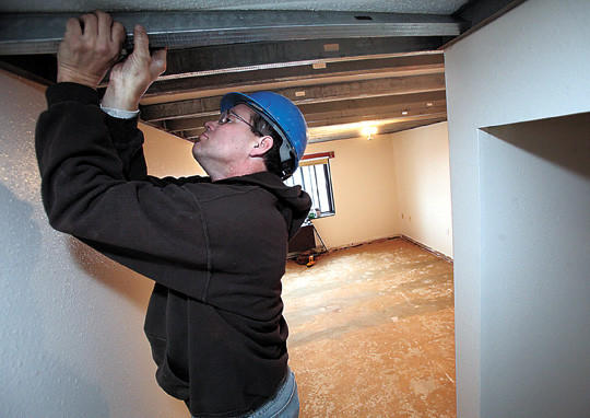 Scott Anderson with Kyburz-Carlson Construction installs a ceiling support system in one of the 24 apartments being remodeled at the Sherman Apartments in downtown Aberdeen.
