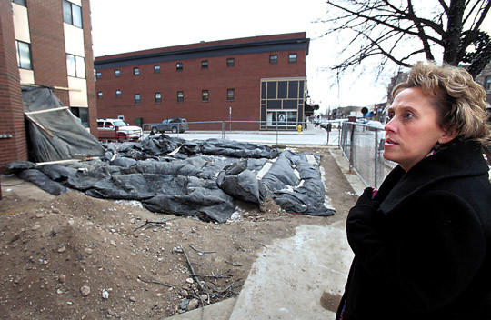 Jody Zueger, executive director of the Aberdeen Housing Authority, right, talks about the remodeling project going on at the Sherman Apartments in downtown Aberdeen. In the background are the covered footings and work area outside the apartment complex.