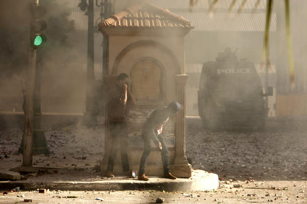 Protesters hide from police during clashes in Alexandria,