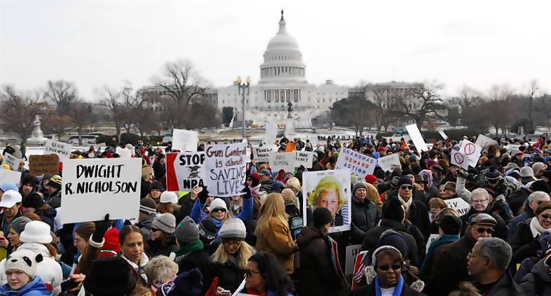 People carry signs as they gather near the Capitol to participate in the March on Washington for Gun Control.