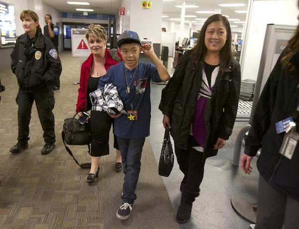 Laura Herzog, family support coordinator with Honoring Our Fallen, Kyle Bolor, 12, and his mom Kelly go through security at Bob Hope Airport on their way to a Sacramento Kings game. Southwest Airlines provided complimentary travel to sit courtside at a Kings game, where Kyle would be the guest of honor. Kyle's father was killed in Iraq 10 years ago.