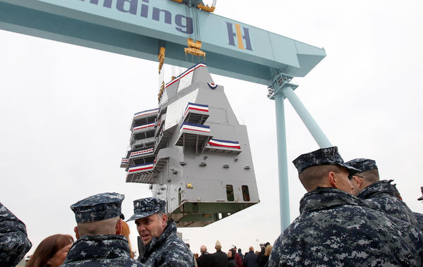 Crew members of the carrier Gerald R. Ford watch as the island is lifted into position Saturday at Newport News Shipbuilding.