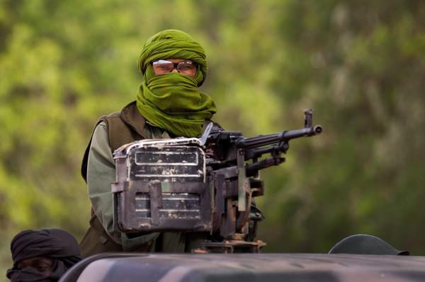 A Malian soldier rides in a pickup truck on patrol along a road north of Diabaly on Saturday. French and Malian forces reportedly seized the key northern city of Gao during the day.