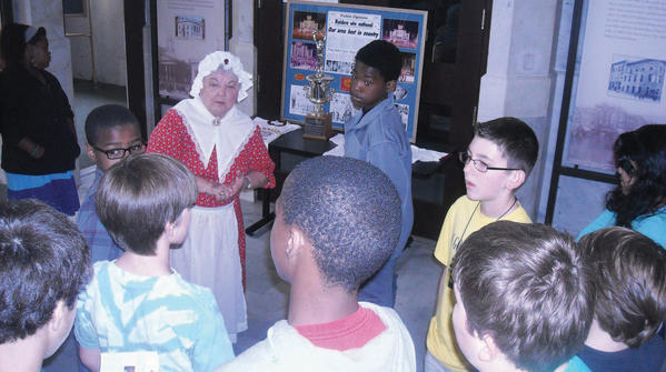 Costumed volunteer Frances Humelsine answers a question from a student from Benjamin Chambers Elementary School during a tour in 2012.