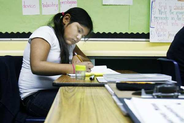 Maria Cruz Castaneda Avila works on a math problem at Horace Mann Elementary School in Glendale. Maria is the youngest of four Glendale siblings who recently lost their mom to cancer, and their father died several years ago.