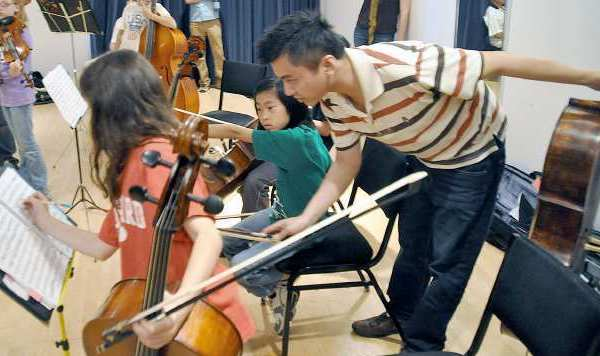 Tao Ni, the associate principal cellist of the L.A. Philharmonic, works with members of the Los Angeles Children's Chamber Orchestra. He will perform with the orchestra Feb. 3 for a fundraiser to help orchestra members get to Carnegie Hall in April.