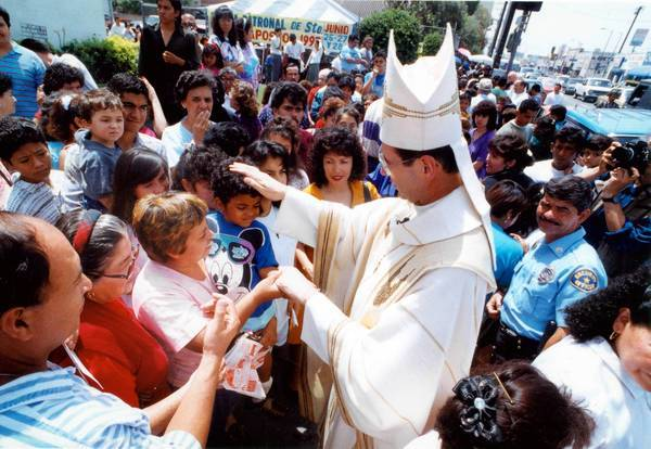 Archbishop Roger M. Mahony blesses parishioners at St. Thomas the Apostle Church in 1992. The revelations about his mishandling of two pedophile priests threaten to tarnish his legacy of fighting for immigrants, an effort that was widely acknowledged as a triumph in his tenure.