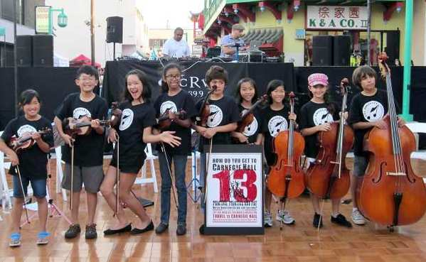 Members of the Los Angeles Children's Orchestra open their cases in Chinatown to help raise money for their trip to New York.