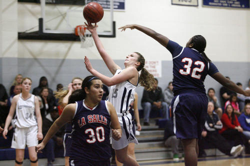 Flintridge Prep's Lacy Coan, center, shoots the ball and is blocked by La Salle's Kandyce Smith during a game at Flintridge Prep on Saturday, January 26, 2013.