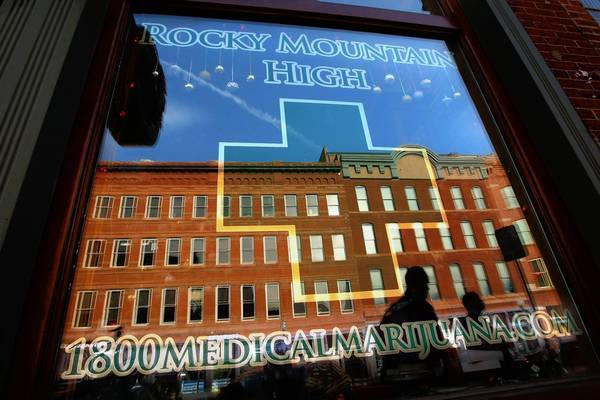 Pedestrians are reflected in the main window of the Rocky Mountain High marijuana dispensary in downtown Denver. Venture capitalists are trying to figure out how to capitalize on the marijuana market in the wake of voter approval of recreational pot use in the state.