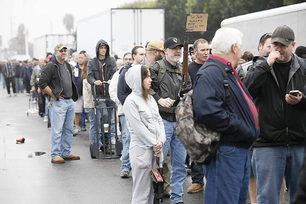 Rene Maeseele advertises his son's Polytech M14 rifle for sale while standing in line with thousands of others to get into the Crossroads of the West Gun Show at the O.C. Fairgrounds on Saturday.