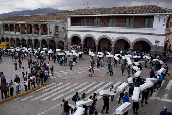 People carry the coffins of relatives killed in massacres executed by the Shining Path militant group and Peru's Army in Peru's southern district of Chungui between 1984 and 1985, during a funeral ceremony in Ayacucho city