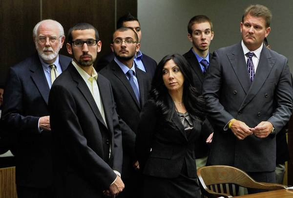 Four of the so-called Irvine 11 are flanked by their attorneys at a hearing in 2011. Ten of the students have filed an appeal in Orange County Superior Court. Charges against an 11th student were dropped.