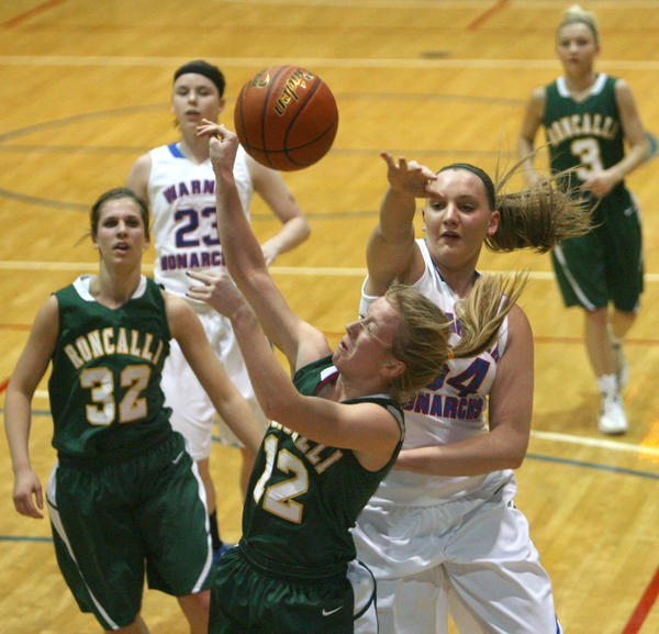 Warner's Miranda Ristau, right, blocks the shot attempt of Aberdeen Roncalli's Paige Sommers, center, during the first half of Saturday night's game at the Aberdeen Civic Arena. Looking on are Roncalli's Abby Dockter (32) and Taylor Hanson (3) and Warner's Jaici Schlosser (23).