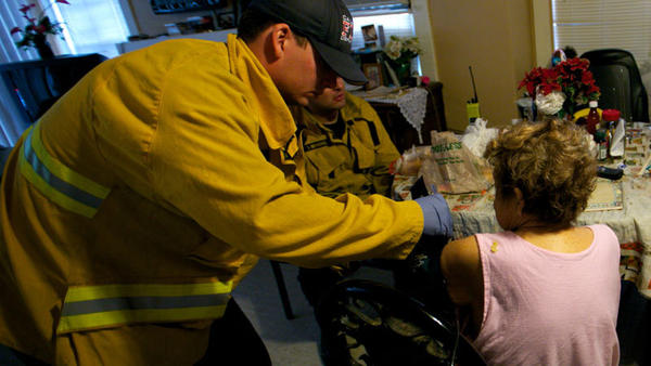 A Calexico firefighter checks the blood pressure of an 82-year-old woman suffering from diabetes on Friday. As the Affordable Care Act ramps up, many uninsured resort to emergency responders to access care.