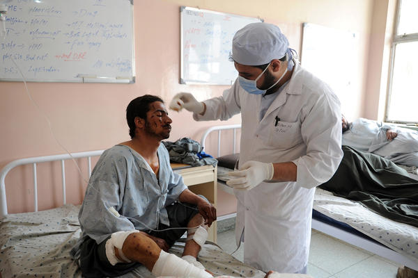 A wounded Afghan police officer is treated at a hospital in southern Afghan city of Kandahar. Eight police officers and three detainees were killed late Saturday by a powerful homemade bomb in Kandahar, officials said.